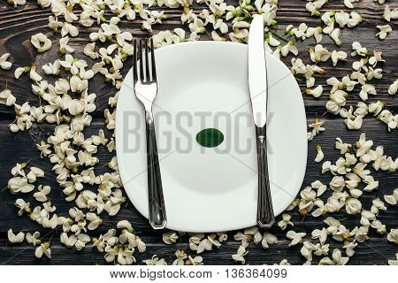 Plate with fork and knife in white acacia blossoming flower petals decorative frame on dark wooden background