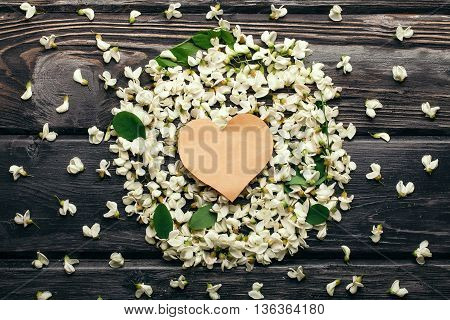 Empty heart note on white acacia blossoming flower petals and green leaves arranged in round shape on dark wooden background