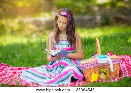 Girl learning on summer vacation and reading book in the meadow