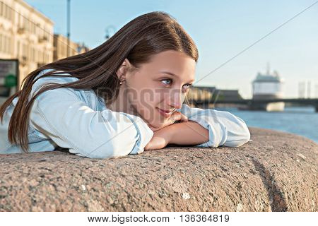 beautiful girl walks on the promenade at sunset