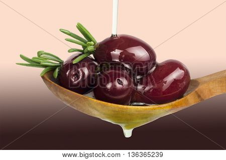 Red olives in oil. Olives on a spoon. Olive oil poured on olives.