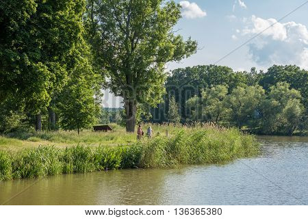 MEM, SWEDEN - JUNE 25, 2016: Cyclists ride along  Gota Canal during midsummer  in Sweden. Mem is the gate to Gota Canal from the Baltic sea on the east coast of Sweden.