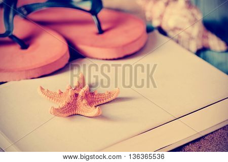 closeup of a yellow starfish and a pair of colorful orange flip-flops on a book, with a conch in the background, and a retro effect