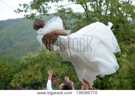 Men throw beautiful bride in white wedding dress and veil in air on green landscape background