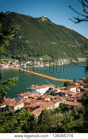 SULZANO ITALY - JUNE 27: Christo's Floating Piers installation in lake Iseo seen from Via Valeriana on June 27th 2016. The bulgarian artist's project connects Montisola and San Paolo island to the mainland using a modular floating dock system