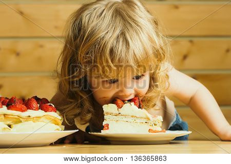 cute little boy child with long blonde hair eating tasty creamy pie or cake with red strawberry fruit
