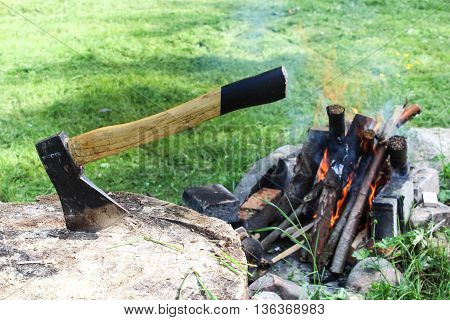 The old axe stuck in the log on the background of fire