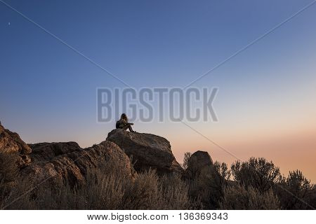 Sunset at the top of Antelope Island with silhouette of female sitting on rocks near Salt Lake City, Utah.
