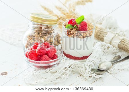 Granola with rasberry and yogurt in glass, copy space