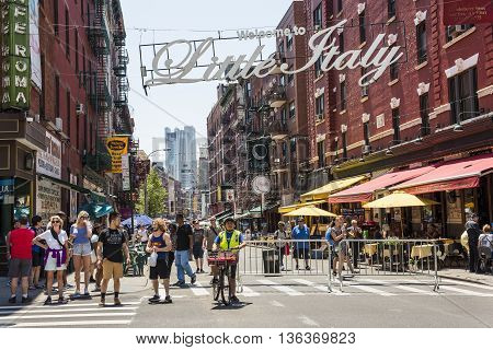 New York, USA - June 18, 2016: Busy street with pedestrians in Little Italy with a welcome sign in New York City