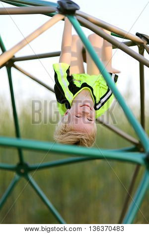 Happy Young Child Climbing Jungle Gym At Playground