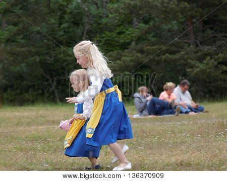 VADDO SWEDEN - JUNE 23 2016: Smiling children wearing traditional costume running on the grass celebrating the Midsommer in Sweden June 23 2016