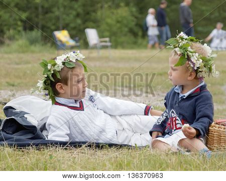 VADDO SWEDEN - JUNE 23 2016: Two young boys with flowers in the hair laying on the grass celebrating the Midsommer in Sweden June 23 2016