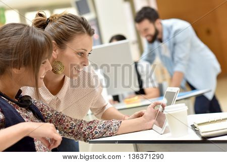 Young women in office working on digital tablet