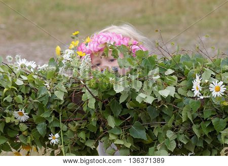 VADDO SWEDEN - JUNE 23 2016: Litte girl wearing flowers in the hair making the maypole celebrating the Midsommer in Sweden June 23 2016