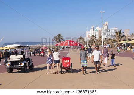 DURBAN SOUTH AFRICA - JUNE 26 2016: Many early morning unknown people and golf cart on paved promenade on Golden Mile beach front against city skyline in Durban South Africa