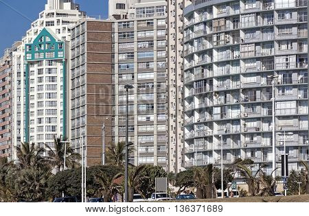 DURBAN SOUTH AFRICA - JUNE 26 2016: Early morning parked vehicles and palm trees against residential and commercial buildings on beach front in Durban South Africa