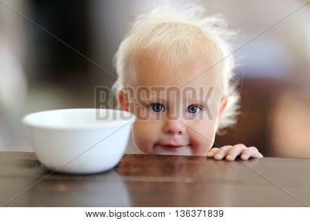 Cute Little One Year Old Baby Girl Next To Cereal Bowl In Kitchen