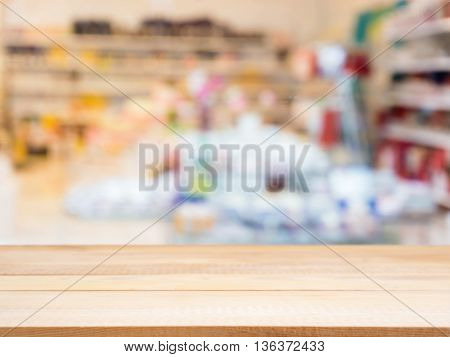 Wooden board empty table in front of blurred background. Perspective light wood table over blur in interior of abstract shop. Mock up for display or montage your product.