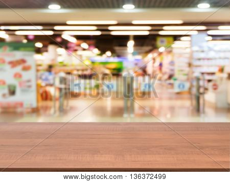 Wooden board empty table in front of blurred background. Perspective dark wood over blur in entrance area of supermarket. Mock up for display or montage your product.