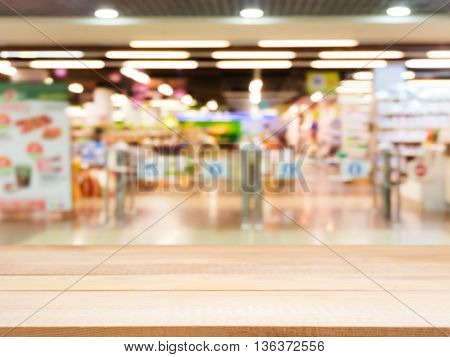 Wooden board empty table in front of blurred background. Perspective light wood over blur in entrance area of supermarket. Mock up for display or montage your product.