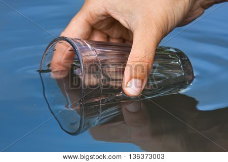 hand scooping water from a clean pond with a glass