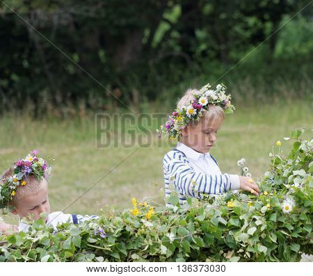 VADDO SWEDEN - JUNE 23 2016: Young boys help making the maypole celebrating the Midsommer in Sweden June 23 2016