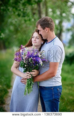 couple in love with a bouquet of flowers are embracing in the park.