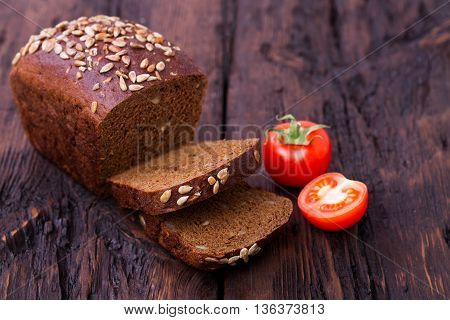 Rye bread sunflower seeds and tomato on an old wooden table