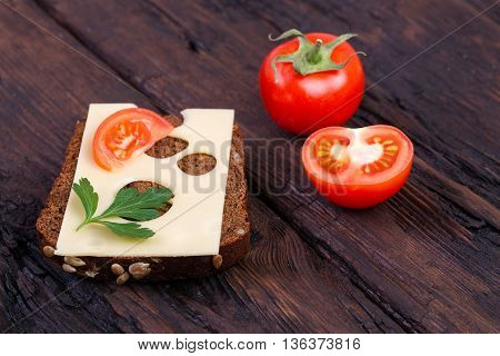 Rye bread cheese tomato and parsley on an old wooden table