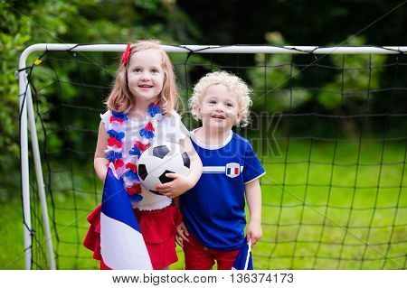 Children cheering and supporting French national football team. Kids fans and supporters of France during soccer championship. Family with little girl and boy watch football game.