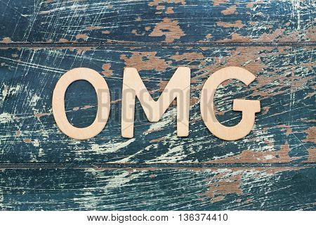 OMG letters on rustic, scratched wooden surface