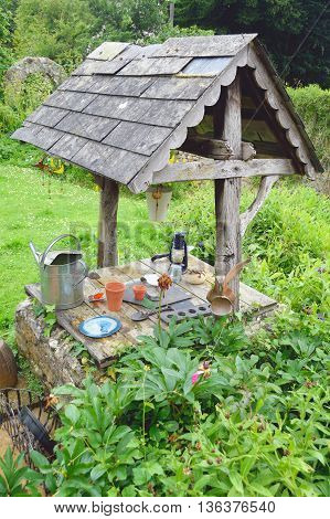 Old wooden decorative wishing well in garden