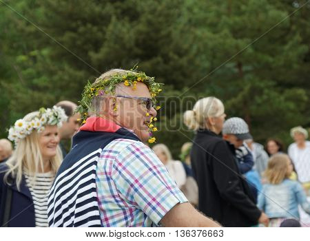VADDO SWEDEN - JUNE 23 2016: Smiling senior man with flowers in the hair dancing around the the maypole celebrating the Midsummer in Sweden June 23 2016