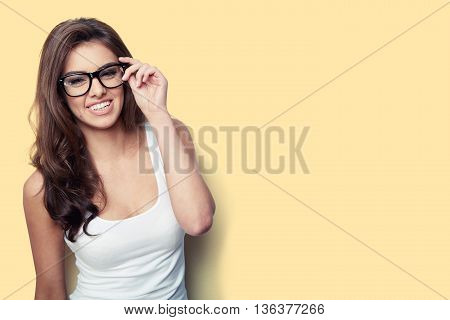 Smiling student girl in white shirt and glasses on yellow background