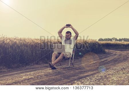 Businessman sitting in the middle of the field and working on laptop and talking on the phone. Relax and work. Outdoor work. In the nature. Successful deal.