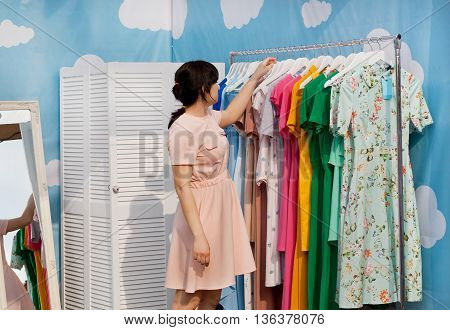 KYIV, UKRAINE - JUN 4, 2016: Beautiful woman making choice in showroom of bright fashion store with colorful dresses on June 4, 2016. Kiev is the 8th most populous city in Europe.