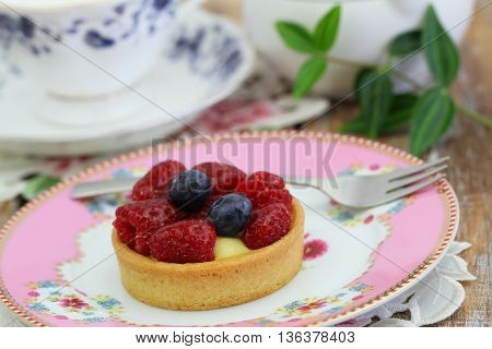 Delicious crunchy tartelette with custard, fresh raspberries and blueberries on pink plate