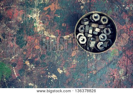 Filtered nuts in a tin can on colorful wooden background