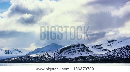 Dramatic clouds over mountains covered with snow in the cold arctic environment in Svalbard.