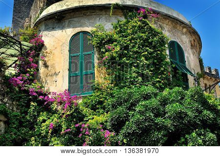 round tower with window shutters and bougainvilleas in village Portovenere, Cinque Terre