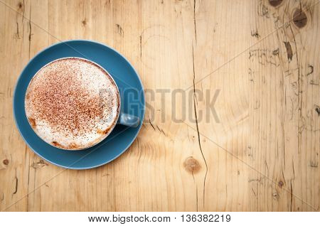 Fresh cup of coffee on a wooden table background in the cafe