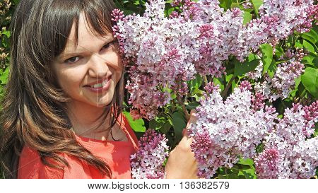 Young smilling woman with lilac. Spring 2016.