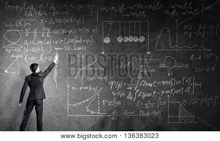 Man in suit standing with back and drawing physics formulas