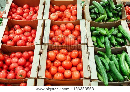 boxes with cucumbers and tomatoes in supermarket. Healthy Eating