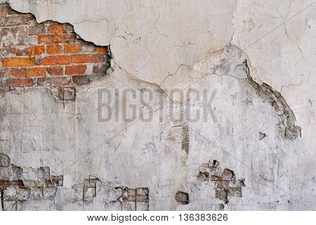 the old textured brick wall with the destroyed plaster for an abstract background or for wallpaper