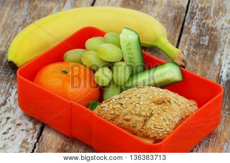 Healthy school lunch box containing whole grain roll with cheese and lettuce, grapes, cherry tomatoes and cucumber sticks