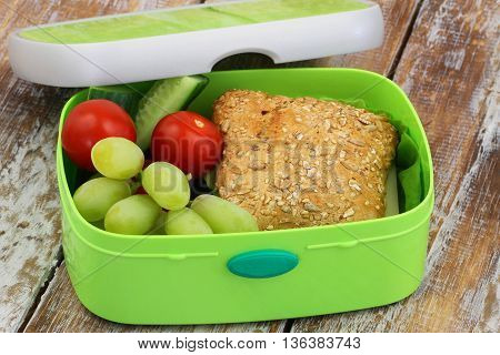 Healthy school lunch box containing whole grain roll with cheese and lettuce, cucumber sticks, grapes, mandarine and banana