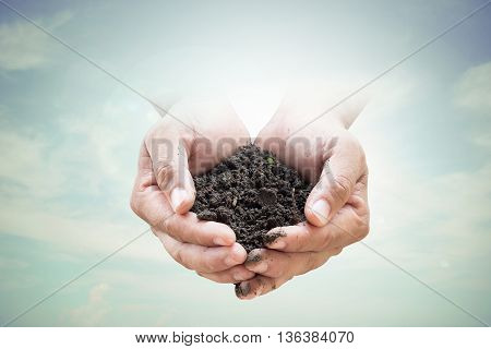 Human hands holding soil emerges from the sky in the background blurred.Environment Day concept. Ecology concept.