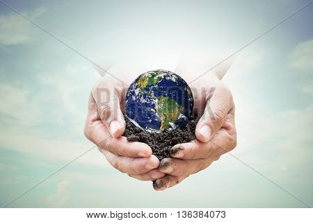 Human hands holding soil emerges from the sky in the background blurred. Create a new world. loves the world.Environment Day concept.Ecology concept. Elements of this image furnished by NASA.